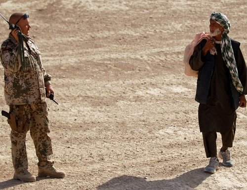 An Afghan man walks past a German Bundeswehr soldier talking on the radio near Camp Marmal on September 25, 2010, in Mazar-e-Sharif, Afghanistan. In early 2020, Germany joined a European effort to develop a new generation of interoperable radio equipment. (Photo by Miguel Villagran/Getty Images)