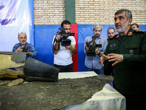 Gen. Amir Ali Hajizadeh, right, Iran's head of the Revolutionary Guard's aerospace division, speaks to media next to debris from a downed U.S. drone reportedly recovered within Iran's territorial waters and put on display by the Revolutionary Guard in the capital Tehran on June 21, 2019. (Meghdad Madadi/AFP/Getty Images)
