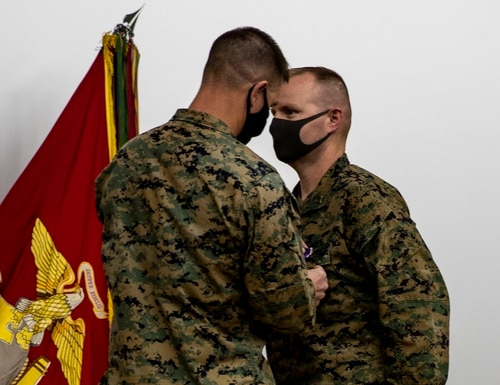 U.S. Marine Corps Brig. Gen. Kyle Ellison, commanding general for 3rd Marine Expeditionary Brigade, left, awards Capt. Kevin W. Leishman, an anti-terrorism force protection officer, right, with the Purple Heart medal at the base theater, Camp Courtney, Okinawa, Japan, Feb. 24. (Cpl. Francesca Landis/Marine Corps)