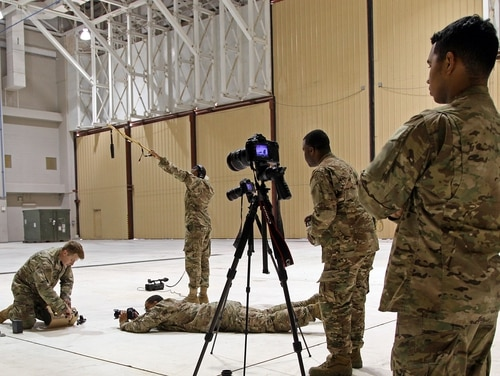 Soldiers assigned to the Military Information Support Task Force-Central Production Development Detachment capture a PYSOPS specialist setting up a loudspeaker at Al Udeid Air Base, Qatar, in 2016. (Army)