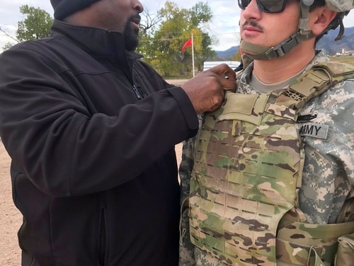 Damon Brant, a new equipment trainer, ensures the proper wear of a new body armor system by Spc. Creed Cooney, an explosive ordnance disposal technician with the 62nd Ordnance Company, during a field test at Fort Carson, Colo., Oct. 18. (Staff Sgt. Lance Pounds/Army)