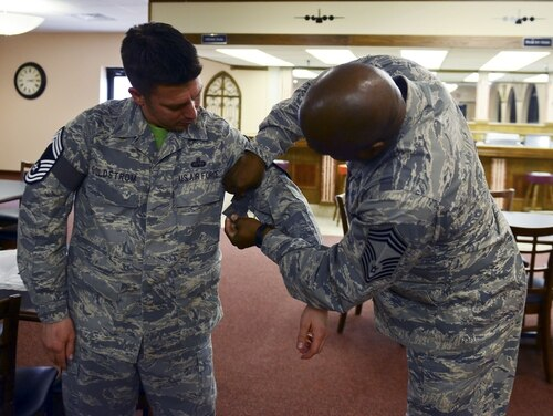 Chief Master Sgt. Joel Brown puts chief master sergeant stripes on Senior Master Sgt. Antonio Goldstrom in November 2014 at Dyess Air Force Base, Texas. (Airman 1st Class Kedesha Pennant/Air Force)