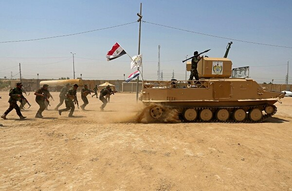In this July 18, 2017, file photo, Shiite Volunteer fighters from the Imam Ali Brigade, an armed faction with the Iraqi Popular Mobilization Forces, train at their camp, in Najaf, 100 miles (160 kilometers) south of Baghdad, Iraq. (Anmar Khalil/AP)