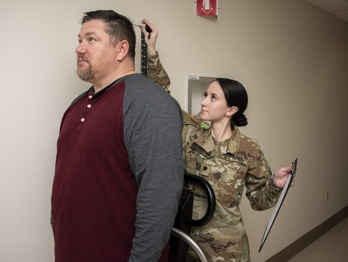 Army Spc. Breann Messina, metabolic and bariatric surgery clinical reviewer, checks a patient's height and weight at the Bariatric Surgery Clinic at Brooke Army Medical Center, Fort Sam Houston, Texas, Jan. 29, 2020. Under ongoing reforms in the military health system, fewer non-uniformed patients will be treated by military medical personnel. (Jason W. Edwards/Army)