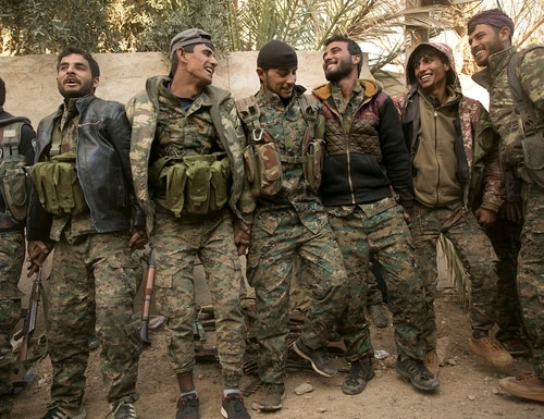 U.S.-backed Syrian Democratic Forces (SDF) fighters celebrate their territorial gains over Islamic State militants in Baghouz, Syria, move to a camp Tuesday, March 19, 2019. (Maya Alleruzzo/AP)