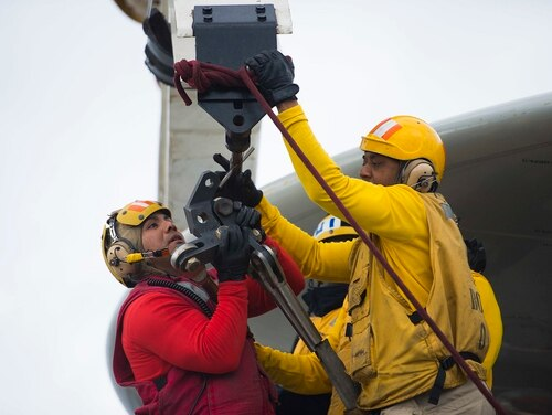 Sailors attach crash and salvage equipment to a crane during a simulated emergency exercise on the flight deck of the forward-deployed aircraft carrier Ronald Reagan. Sailors could soon see longer overseas sea tours if a Navy request to DoD is approved. (MC2 Paolo Bayas/Navy)