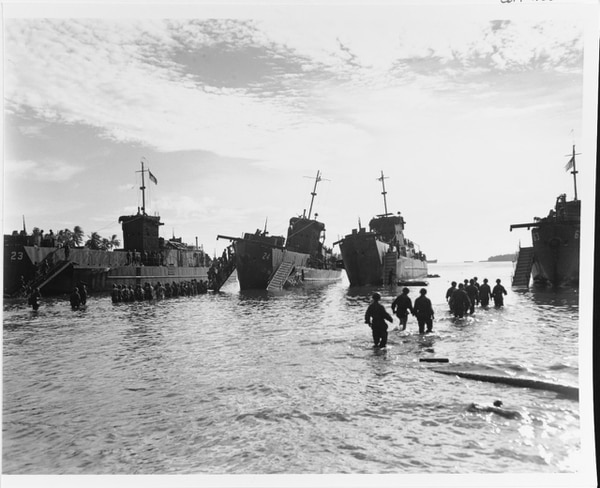 Marines unloading landing craft on a Rendova Island beach, 4 July 1943. They are unloading in a hurry after a bomb struck between the two craft in the center. (National Archives)