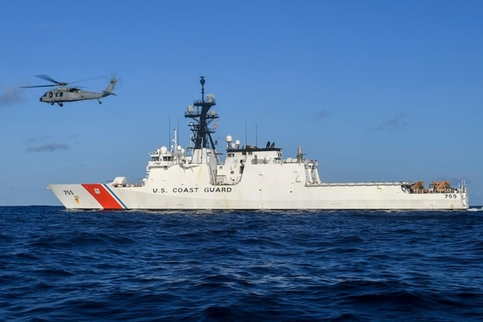 In this Aug. 25, 2020, photo provided by the U.S. Navy, an MH-60S Sea Hawk helicopter hovers next to the Legend-class cutter USCGC Munro in the Pacific Ocean. (MC3 Madysson Anne Ritter/U.S. Navy via AP)