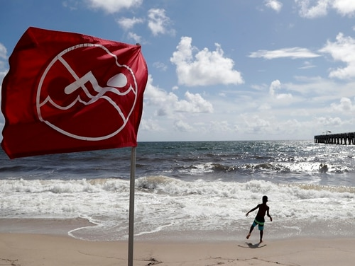 A boy plays on the beach as a No Swimming flag flies, Saturday, Aug. 31, 2019, in Lake Worth, Fla. Hurricane Dorian is bearing down on the northwestern Bahamas as forecasters say Dorian is then expected to go up the Southeast coastline. (Lynne Sladky/AP)