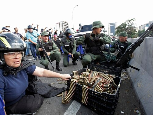 An anti-government protester sits by ammunition being used by rebel troops rising up against Venezuelan President Nicolas Maduro. (Boris Vergara/AP)