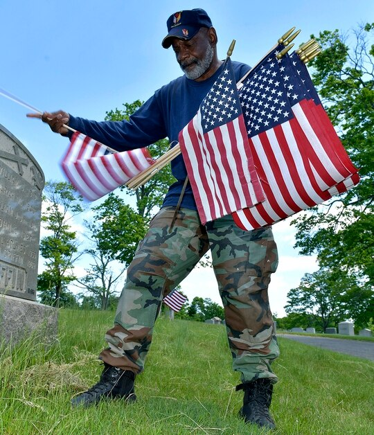 Bob Workman of Boston, a retired Marine gunnery sergeant, and past commander of the Boston Police VFW, replaces flags at veteran's graves ahead of Memorial Day on May 27, 2021, in the Fairview Cemetery in Boston. (Josh Reynolds/AP)