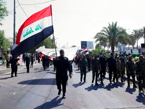 Iran-backed militia fighters march in central Baghdad, Iraq, Tuesday, June 29, 2021. (AP Photo/Khalid Mohammed)