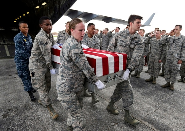 In this Sept. 13, 2018, photo, military personnel perform an honorable carry of flag-draped transfer cases containing remains of unidentified service members from a C-17 Globemaster plane to waiting trucks, at Offutt AFB in Bellevue, Neb. The remains were gathered through various DPAA missions in Europe and are being delivered to the lab at Offutt to begin the identification process. (Nati Harnik/AP)