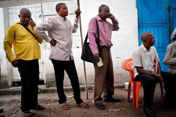 Congolese independent electoral commission (CENI) officials wait in line to be paid, as results are still being tallied for the presidential election at a local results compilation center in Kinshasa, Congo, Sunday, Jan. 6, 2019. CENI said the publication of preliminary results would be postponed. (Jerome Delay/AP)
