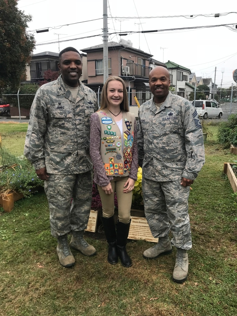 Emma in 2018 with Air Force Col. Otis Jones, then base commander, and Chief Master Sgt. Elvin Young, then base command chief, after she presented the sensory garden to Yokota Air Base. (Courtesy of Operation Homefront)