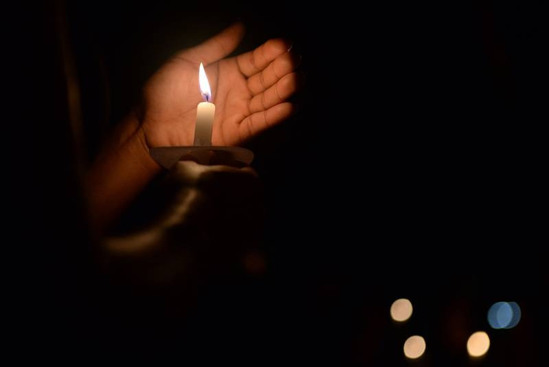 A candle burns during Lights for Lives on Biloxi Beach