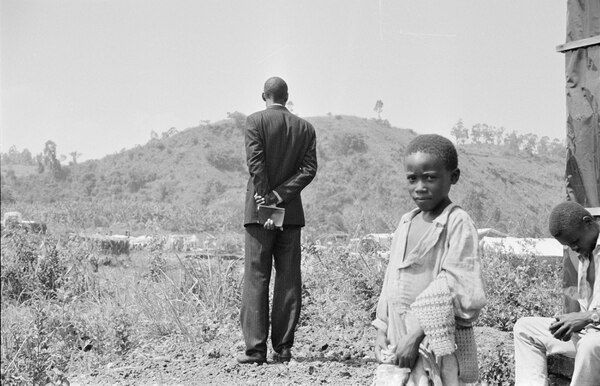 Boy in Rwanda with man in background. Photo taken by Eric Greitens during humanitarian mission