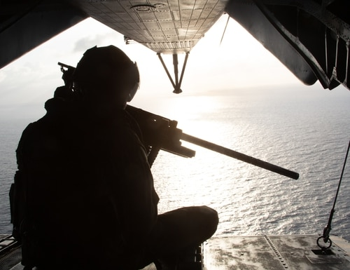 A U.S. Marine crew chief with the Special Purpose Marine Air-Ground Task Force - Southern Command mans the rear of a CH-53 during a refueling flight off the coast of Honduras, Aug. 13, 2019. (U.S. Marine Corps photo by Cpl. Mathew Rosado)