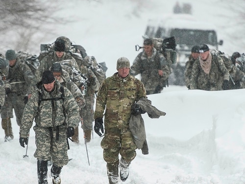 Vermont National Guard soldiers on a training exercise emerge from a closed section on Vermont 108 in Cambridge, Vt., just below Smuggers Notch on Wednesday night, March 14, 2018, after six soldiers were swept approximately 300 meters by an avalanche. (Ryan Mercer/The Burlington Free Press via AP)