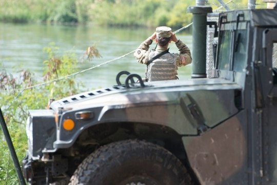 A soldier from the Texas National Guard scans the shores of the Rio Grande River in Starr County, Texas. (Sgt. Mark Otte/Texas Military Department)