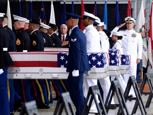 In this Aug. 1, 2018, file photo Vice President Mike Pence and Navy Rear Adm. Jon Kreitz, deputy director of the POW/MIA Accounting Agency, right, watch as military members carry transfer cases from a C-17 at a ceremony marking the arrival of the remains believed to be of American service members who fell in the Korean War at Joint Base Pearl Harbor-Hickam, Hawaii. (Susan Walsh/AP)