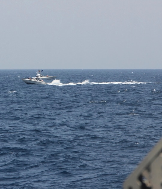An Iranian Islamic Revolutionary Guard Corps Navy fast in-shore attack craft speeds near U.S. naval vessels transiting the Strait of Hormuz on May 10, 2021. (U.S. Navy via AP)