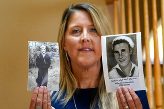 Teri Mann Whyatt displays photos of her uncle, William Edward Mann, who died on the battleship Arizona during the bombing of Pearl Harbor, at her home Wednesday, July 14, 2021, in Newcastle, Wash. (AP Photo/Elaine Thompson)