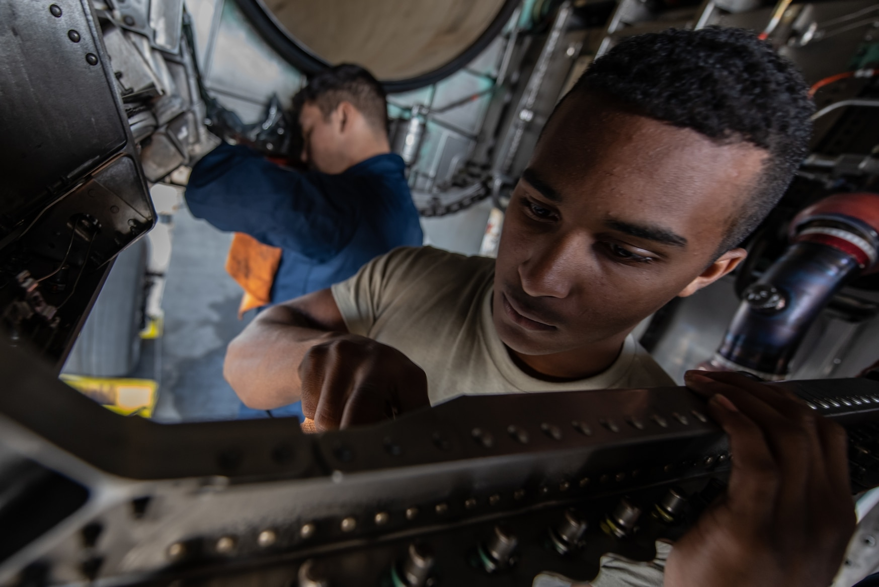 Airman 1st Class Nathaniel West, 18th Aircraft Maintenance Squadron crew chief, cleans an F-15 Eagle engine bay compartment Jan. 18 at Kadena Air Base, Japan. (Staff Sgt. Micaiah Anthony/Air Force)