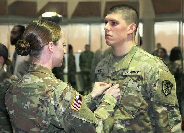 Cpl. Noel Williams of U.S. Army Intelligence and Security Command pins private first class rank on Zachary Grasee during a promotion ceremony. Soldiers like Grasee, who are looking to eventually move up to sergeant and staff sergeant, now have a better chance of being selected if they're properly qualified and eligible. (Tani Murphy/Army)