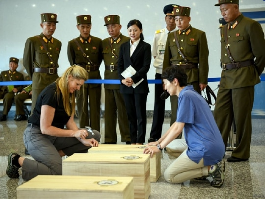 Defense POW/MIA Accounting Agency forensic anthropologist Jennie Jin, bottom right, secures one of the 55 cases of remains of service members as North Korean officials watch in Wonsan, Democratic People's Republic of Korea, July 27, 2018. The cases were transported via military aircraft to Osan Air Base, Republic of Korea, for initial review before being transferred to DPAA's forensic laboratory at Joint Base Pearl Harbor-Hickam, Hawaii. (Sgt. 1st Class David J. Marshall/Army)