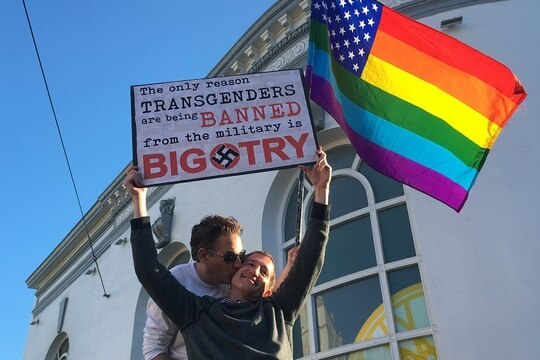 Nick Rondoletto, left, and Doug Thorogood, wave a rainbow flag and a sign during a July 26, 2017, protest in San Francisco. (Olga R. Rodriguez/AP)