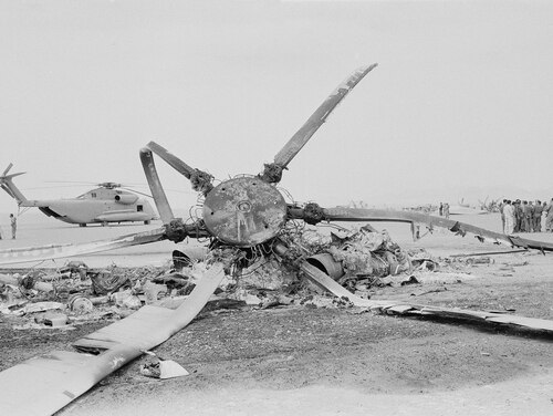 The rotor blades of a burned-out U.S. helicopter create a stark silhouette against the desert skies of eastern Iran, where the American commando mission to rescue the hostages proved impossible after equipment failure, seen April 27, 1980. In background is a U.S. helicopter that was also left behind when the mission was aborted. (AP Photo)