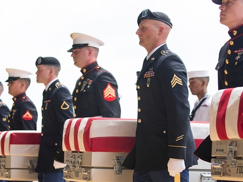 U.S. military honor guard carry the presumed remains of Korean War soldiers at Hangar 19 Joint Base Pearl Harbor-Hickam on Aug. 1, 2018 in Honolulu, Hawaii. The remains of 55 service members were flown to Hawaii after being handed over by North Korea. (Kat Wade/Getty Images)