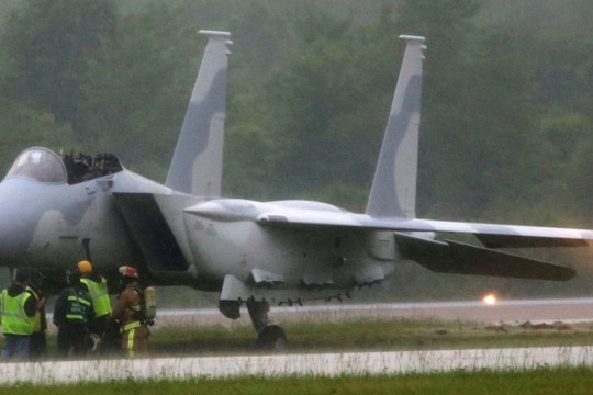 Emergency crews are on the scene where two pilots ejected from a F-15QA fighter aircraft on a runway at MidAmerica St. Louis Airport at about 7:30 a.m.Tuesday in Mascoutah, Ill. (Laurie Skrivan/St. Louis Post-Dispatch via AP)