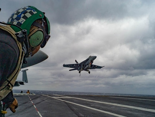 Flight deck crewmen watch the approach of aircraft during the carrier's Composite Unit Training Exercise (Mark D. Faram/Staff)