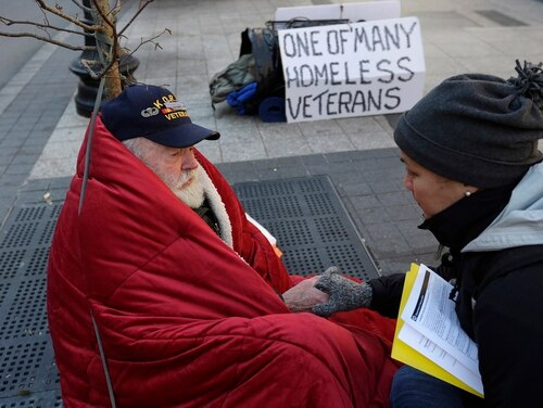 In this November 2013 photo, a Korean War veteran experiencing homelessness speaks with a Boston Health Care outreach coordinator on a sidewalk in that city. (Steven Senne/AP)