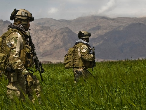 Special Forces soldiers patrol a field in Farah, Afghanistan, alongside Afghan National Army commandos. The Army is investigating allegations of lowered training standards at the school that trains soldiers into Green Berets. (Spc. Joseph A. Wilson/Army)