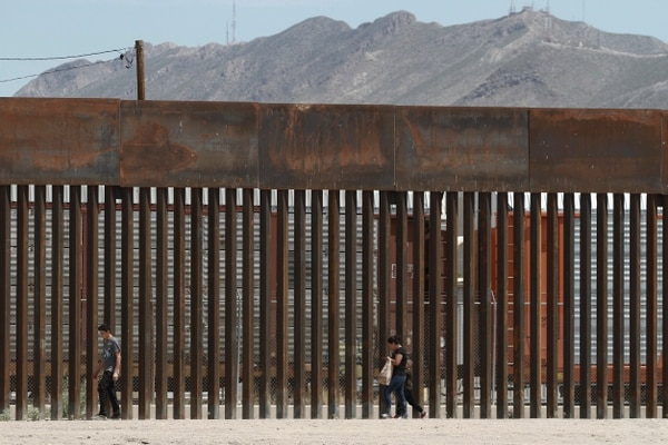 On July 17, three migrants who had managed to evade the Mexican National Guard and cross the Rio Grande onto U.S. territory walk along a border wall set back from the geographical border, in El Paso, Texas, as seen from Ciudad Juarez, Mexico. (Christian Chavez/AP)