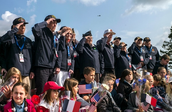 World War II veterans from the United States salute as they pose with local school children at the Normandy American Cemetery in Colleville-sur-Mer, Normandy, France, Monday, June 3, 2019. France is preparing to mark the 75th anniversary of the D-Day invasion which took place on June 6, 1944. (Rafael Yaghobzadeh/AP)