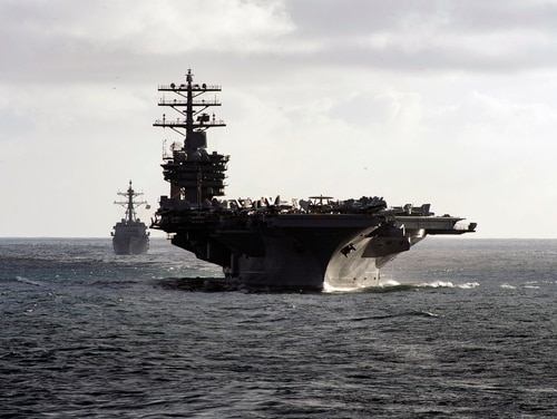 The aircraft carrier USS Nimitz (CVN 68) and Arleigh Burke-class guided-missile destroyer USS Ralph Johnson (DDG 114) steam in formation during a composite training unit exercise as part of the Nimitz Carrier Strike Group (CSG) on May 14, 2020, in the Pacific Ocean. (MCSSA Drace Wilson/U.S. Navy)