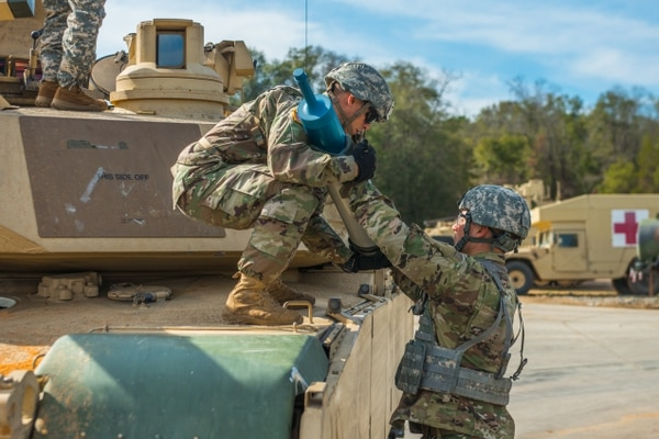 An instructor passes a 120mm training round to a student during an ammunition resupply at the Armor Basic Officer Leader Course. Recent graduates might lead a basic training platoon for their first assignment. (Patrick A. Albright/Army)