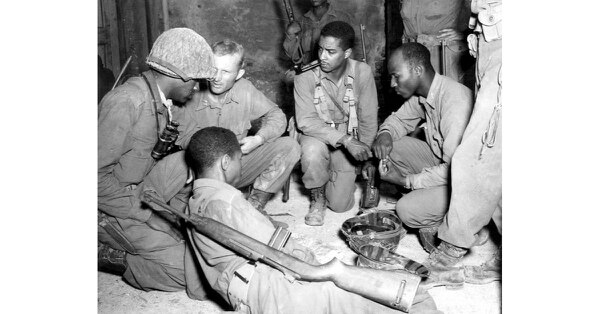 Officers of the 92nd Infantry Division, Company F, 370th Combat Team, look at maps and orders at a farmhouse one-fourth of a mile from the Arno River, Ponsacco Area in Italy. A half hour later these troops successfully crossed the river in the push toward the Gothic Line on Sep. 1, 1944. (U.S. Army)