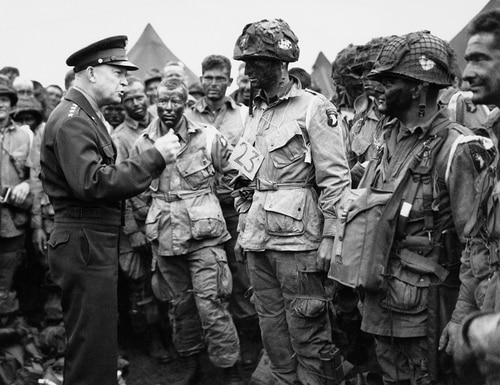 In this June 5, 1944, file photo, U.S. Gen. Dwight D. Eisenhower, left, gives the order of the day to paratroopers in England prior to boarding their planes to participate in the first assault of the Normandy invasion. (U.S. Army Signal Corps via AP)