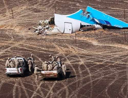 FILE - In this Sunday, Nov. 1, 2015 file photo provided by Russian Emergency Situations Ministry, Egyptian Military on cars approach a plane's tail at the wreckage of a passenger jet bound for St. Petersburg in Russia that crashed in Hassana, Egypt. The Russian passenger plane that crashed in Egypt was brought down by a homemade bomb placed on board in a