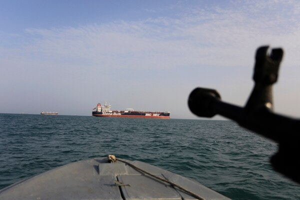 In this July 21 photo, a speedboat of Iran's Revolutionary Guard trains a weapon toward the British-flagged oil tanker Stena Impero, which was seized in the Strait of Hormuz on Friday. (Morteza Akhoondi/Tasnim News Agency via AP)