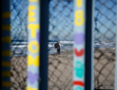 Two people embrace on the U.S. side of the border, seen through the existing border wall on Monday, Jan. 7, 2019, seen from along the beach in Tijuana, Mexico. The White House is looking into the legality of declaring a national emergency to circumvent Congress and begin construction on President Donald Trump's long-promised southern border wall, Vice President Mike Pence said Monday, Jan. 7. (Gregory Bull/AP)