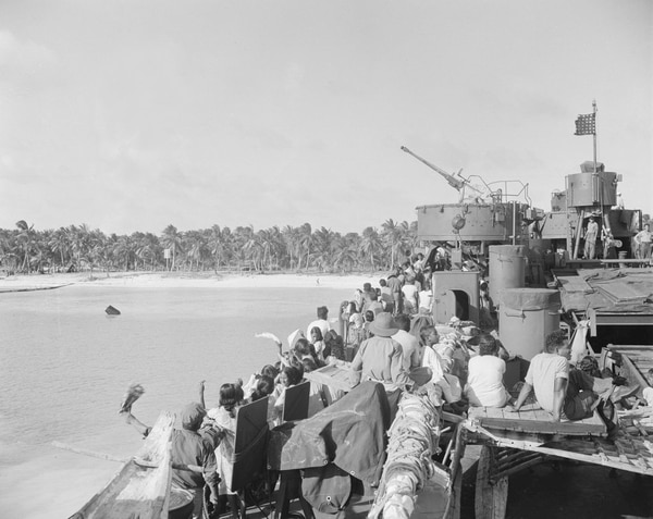 In this March 14, 1946, file photo, people wave farewell to their Bikini Atoll home from a Navy LST transporting them to a new home on Rongerik Atoll 109 miles away. (Clarence Hamm/AP)