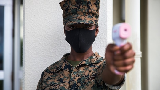 A Marine conducts temperature checks in front of the dining facility on Camp Courtney, Okinawa, Japan, July 13, 2020. (Lance Cpl. Juan Carpanzano/Marine Corps)