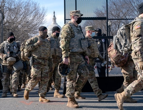 With the U.S. Capitol in the background, members of the National Guard change shifts as they exit through anti-scaling security fencing on Saturday, Jan. 16, 2021, in Washington as security is increased ahead of the inauguration of President-elect Joe Biden and Vice President-elect Kamala Harris. (Jacquelyn Martin/AP)