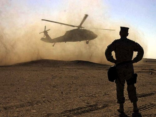 الجنرال جيمس ماتيس من قوة مشاة البحرية الأولى يشاهد الجنرال مايكل هاجي يغادر في طائرة هليكوبتر بلاك هوك في الصحراء الكويتية جنوب العراق يوم الأربعاء 5 فبراير 2003. هاجي ، قائد مشاة البحرية وقائد سلاح مشاة البحرية كان في الكويت لزيارة القوات.  (AP Photo / Laura Rauch)